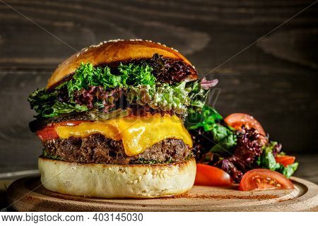 Closeup Photo Of Home Made Fresh Burger With Beef, Onion, Tomato, Lettuce, Cheese And Spices.burger