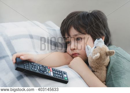Dramatic Portrait Lonely Kid Sad Face Holding Remote Control Sitting On Couch,child Sitting On Sofa