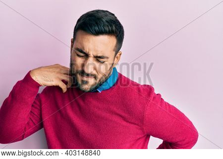 Young hispanic man wearing casual clothes suffering of neck ache injury, touching neck with hand, muscular pain