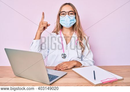 Young beautiful blonde woman wearing doctor uniform and medical mask pointing finger up with successful idea. exited and happy. number one.