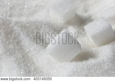 White Sugar Crystals And Cubes Of Refined Cane Sugar Closeup.  Unhealthy Sweets Eating.
