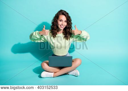 Photo Of Young Girl Sit Floor Hold Netbook Raise Two Hands Show Thumbs Up Wear Green Pullover Sneake