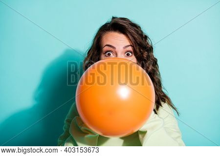 Photo Of Girl Puffing Air Blow Orange Balloon Excited Wear Green Pullover Isolated Blue Color Backgr