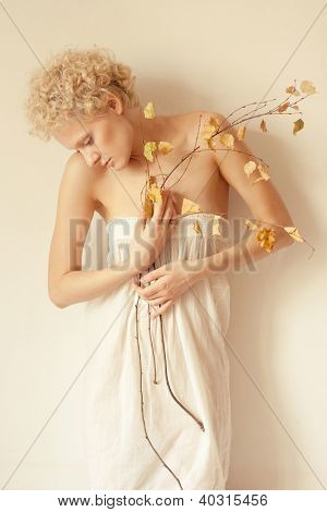 Young scrawny sexy girl with a dry twig in hands