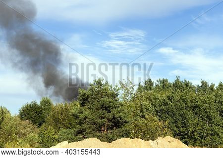 Black Smoke From Burning Forest Trees And Buildings Against A Blue Sky, A Fire With A Lot Of Black D