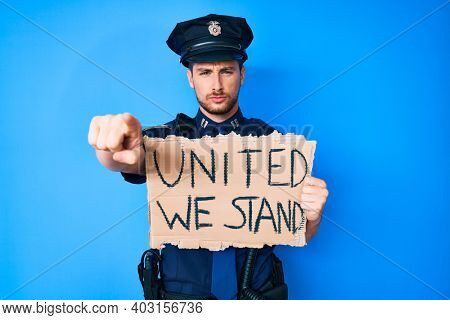 Young caucasian man wearing police uniform holding united we stand banner pointing with finger to the camera and to you, confident gesture looking serious