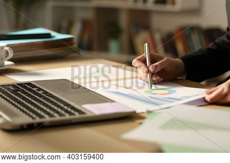 Close Up Of Entrepreneur Hand Working In The Night Checking Paper Chart At Homeoffice