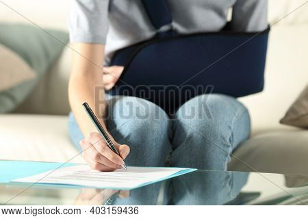 Front View Of A Handicapped Woman With Sling Signing Contract At Home