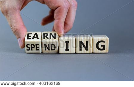 Earning Or Spending Symbol. Businessman Hand Turns Cubes And Changes The Word 'spending' To 'earning