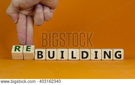 Rebuilding Symbol. Male Hand Turns Wooden Cubes And Changes Words 'building' To 'rebuilding'. Busine