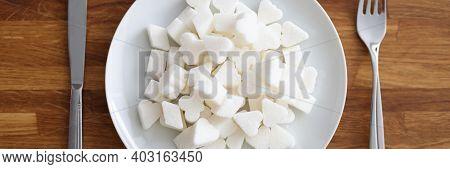 Lot Of Lump Sugar Lying On Plate Near Knife And Fork On Table In Kitchen. High Sugar Consumption As