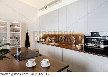 Side View Of Contemporary Interior With Kitchenware In Cabinet, White Kitchen Cupboards, Wooden Coun