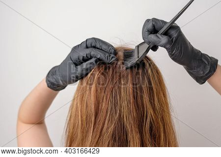 Woman Dyeing Hair Roots Using A Brush. Dyeing Of Gray Roots Of Hair Having A Complex Hair Coloring O