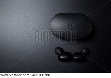 Black Bluetooth Xiaomi Airdots On Black Background With Copyspace. Black Wireless Vacuum Earhpones O