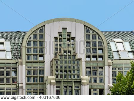 Berlin, Germany - July 30, 2019: Modern Commercial Building With Green Metalic Facade Against Blue S
