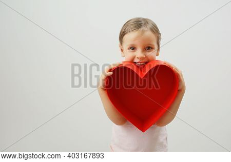 A Happy Smiling Girl Holds A Big Red Heart In Her Hands