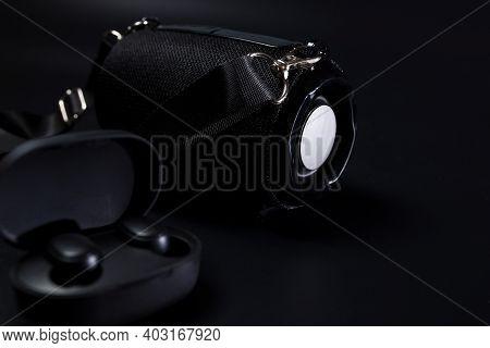 Black Wireless Headphones On Black Background With Black Bluetooth Speaker.
