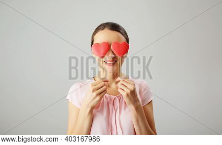 A Happy Girl Holds Ginger Cookies In The Shape Of Red Hearts In Her Hands. Rose Colored Glasses Are