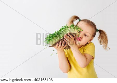 The Child Is Happy With The Sprouts Of Fresh Greens. The Girl Holds In Her Hands A Green Piece Of Th