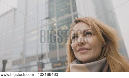 Beautiful Woman Looks Up At High-rise Business. Action. Woman With Confident And Determined Look Loo