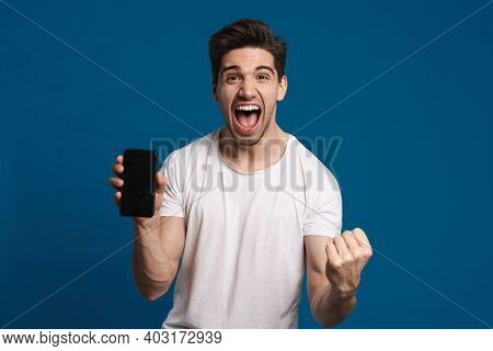 Delighted guy making winner gesture while showing mobile phone isolated over blue background