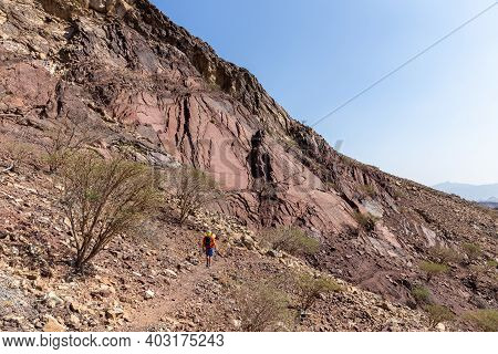 Male Tourist Hiking On Rocky Trail In Hatta, Hajar Mountains, United Arab Emirates. Limestone And Do