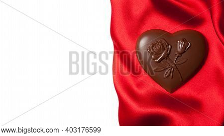 Chocolates Heart Shaped With A Pattern Of Flowers On Red Silk.