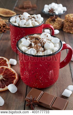 Two Red Cups Of Hot Chocolate With Marshmallow Sprinkled With Cocoa Powder On A Wooden Table With Sl