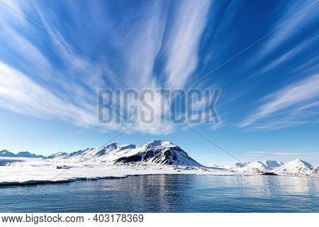 Blue sky, sea and snowy mountains in the beautiful fjords of Svalbard, a Norwegian archipelago between mainland Norway and the North Pole