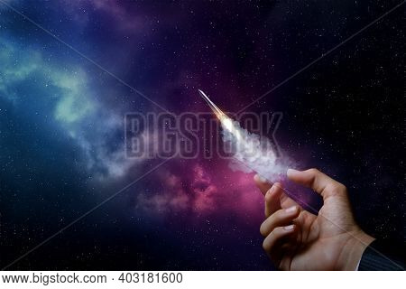 Startup Concept And Promotion. Hand Launches A Rocket On The Background Of Outer Space.