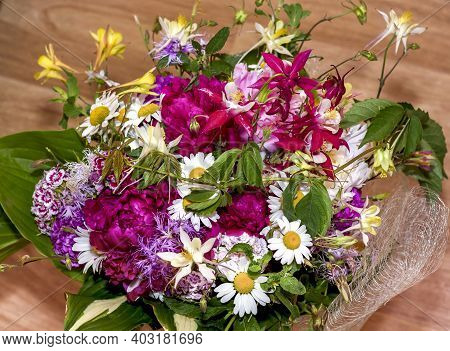 Large Bright Multi-colored Bouquet Of Wildflowers With Peonies And Aquilegia And Large Green Leaves