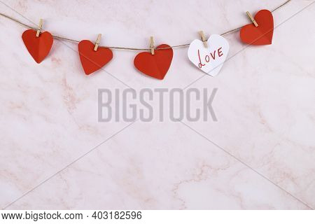 Red Heart Shaped Garland On Over Pink Wall Background. Valentine's Day Garland