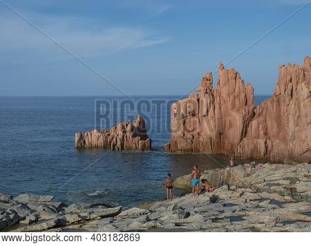 Arbatax, Sardinia, Italy, September 9, 2020: Two Young Men Jumping From Red Rocks, Rocce Rosse At Me