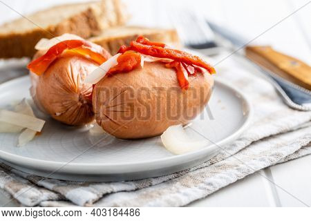 Pickled sausages with onion and red pepper. Marinated food on plate.