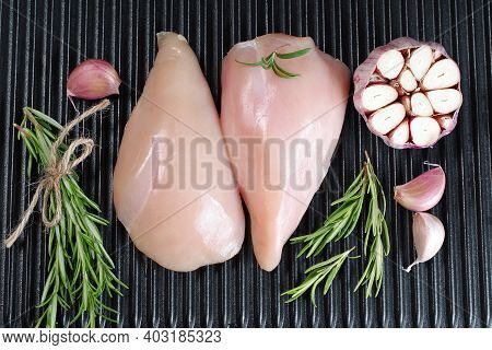 Raw Organic Chicken Breast On A Iron Grill Pan A Black Background.top View .chicken Pieces.raw Chick