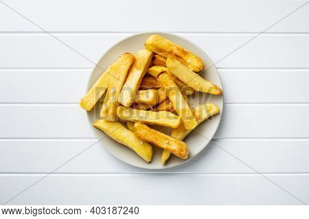Big french fries. Fried potato chips on plate. Top view.