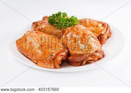 Marinated Chicken Thigh On A White Plate On A Light Background. Chicken For Retail.precooked Food.co