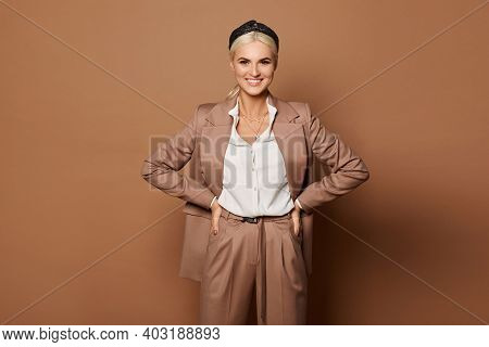 A Happy Young Woman In A White Blouse And Beige Suit Isolated At The Beige Background. Model Woman I