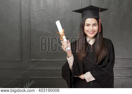 Portrait Of Young Woman In Graduation Gown Smiling And Cheering On Black Background