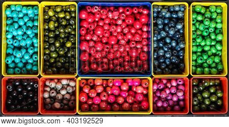 Colourfull Wooden Beads Sorted In Compartments By Colour In Plastic Box Organiser
