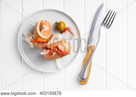 Pickled sausages with onion and red pepper. Marinated food on plate. Top view.