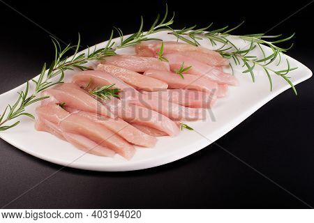 Raw Chicken Meat Slices On Black Background. Culinary Gastronomy Cooking Background.thinly Sliced Ch