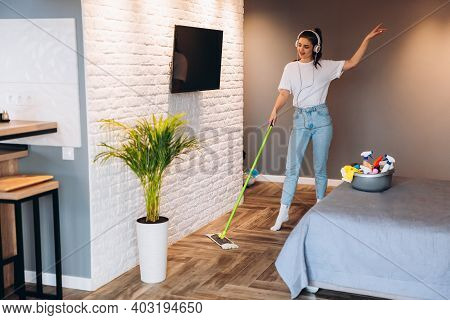 Full Length Photo Of Happy Cheerful Woman Is Washing Floor In Room With Mop Having Fun. Imagine Of H