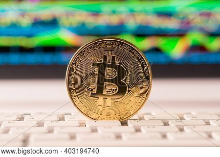 Close Up Photo Of Golden Bitcoin Standing On White Keyboard With Digital Chart Graph On The Backdrop