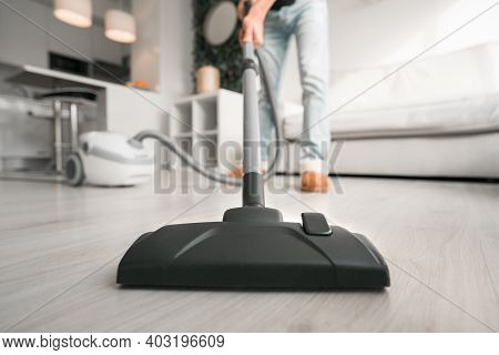 Man Using A Vacuum Cleaner At Home. Man Cleaning House. House Keeping Concept. Close Up On Vacuum Cl