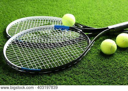 Tennis Rackets And Balls On Green Grass. Sports Equipment