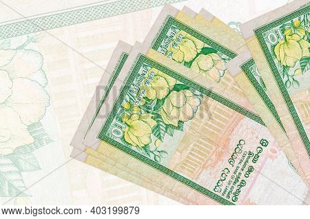 10 Sri Lankan Rupees Bills Lies In Stack On Background Of Big Semi-transparent Banknote. Abstract Pr