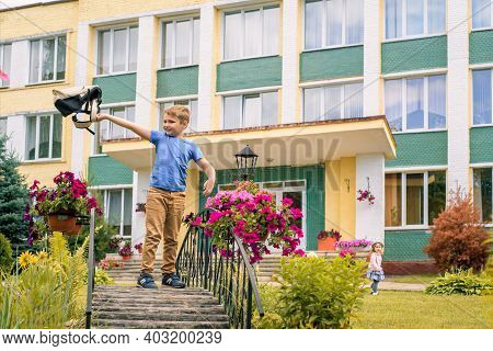 Portrait Of Schoolchild With Backpack Leaping .boy Runs A Backpack Around The School Yard.childhood,