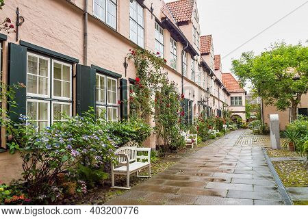 Beautiful Cozy Courtyard With Old Houses And Flowers In The Street Of Old The Town Lubeck, Germany