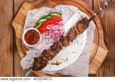 Pork Skewer On A Metal Skewer With Sauce, Sliced Cucumbers, Tomatoes And Onions On A Wooden Tray.